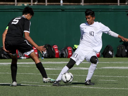 El Paso Del Valle's Iram Baylon passes away from Wichita Falls High School's Alfredo Pacheco Saturday, April 8, 2017, at Memorial Stadium. The Coyotes defeated the Conquistadores 1-0 to advance to their first UIL Soccer State-Tournament.