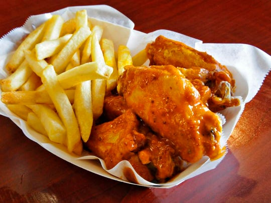 A fresh batch of chicken wings in Buffalo Bleu sauce and French fries at Lily's Wings, Burgers & Things.
