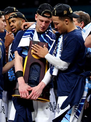Villanova Wildcats guard Donte DiVincenzo (10) and guard Jalen Brunson (1) celebrate with the National Championship trophy after beating the Michigan Wolverines in the championship game of the 2018 men's Final Four at Alamodome.