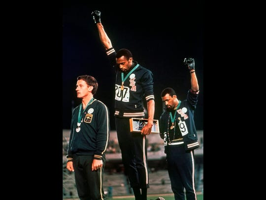 """In this Oct. 16, 1968, file photo, extending gloved hands skyward in protest, U.S. athletes Tommie Smith, center, and John Carlos stare downward during the playing of """"The Star-Spangled Banner"""" after Smith received the gold and Carlos the bronze medal in the 200 meters at the Olympic Games in Mexico City. Australian silver medalist Peter Norman is at left."""
