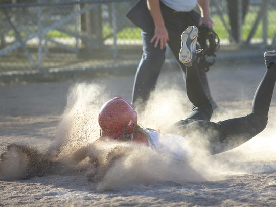 Center Grove High School sophomore Addison Osborn (1) crashes into the dirt as she slides into home plate to score in the eighth inning during the championship game of an IHSAA Softball Sectional at Franklin Central High School, Wednesday, May 23, 2018. Center Grove won 3-1.