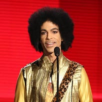 FILE - In this Nov. 22, 2015 file photo, Prince presents the award for favorite album - soul/R&B at the American Music Awards in Los Angeles. Prince's family says an official tribute concert honoring the late icon will take place on October 13, at the U.S. Bank Stadium in Minneapolis. Prince was found dead at his home on April 21, 2016, in suburban Minneapolis. He was 57. (Photo by Matt Sayles/Invision/AP, File)