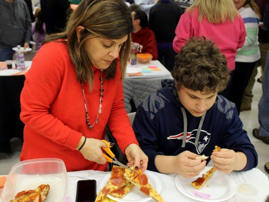 Veteran Pizza Poll participants came prepared with plastic containers for leftovers and scissors to snip off samples. Here, Eileen Belaskas prepares a sample for her son Nicholas.