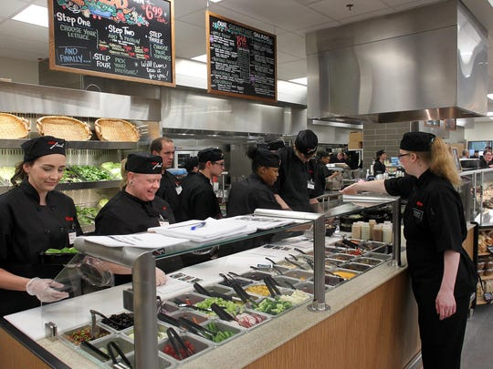 Employees prepare salads inside the new Hy-Vee on Dodge Street in Iowa City.