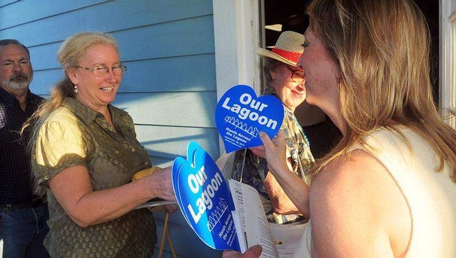 (right) Mary Ann Civic a Geologist of Palm Bay hands out papers about Thursday nights about the Indian River Lagoon workshop held at the Lagoon House Education Center.