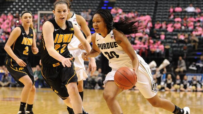 Purdue guard Dee Dee Williams drives past Iowa guard Samantha Logic during the quarterfinals of the Big Ten Women's Basketball Tournament at Bankers Life Fieldhouse, Friday, March 7, 2014, in Indianapolis.