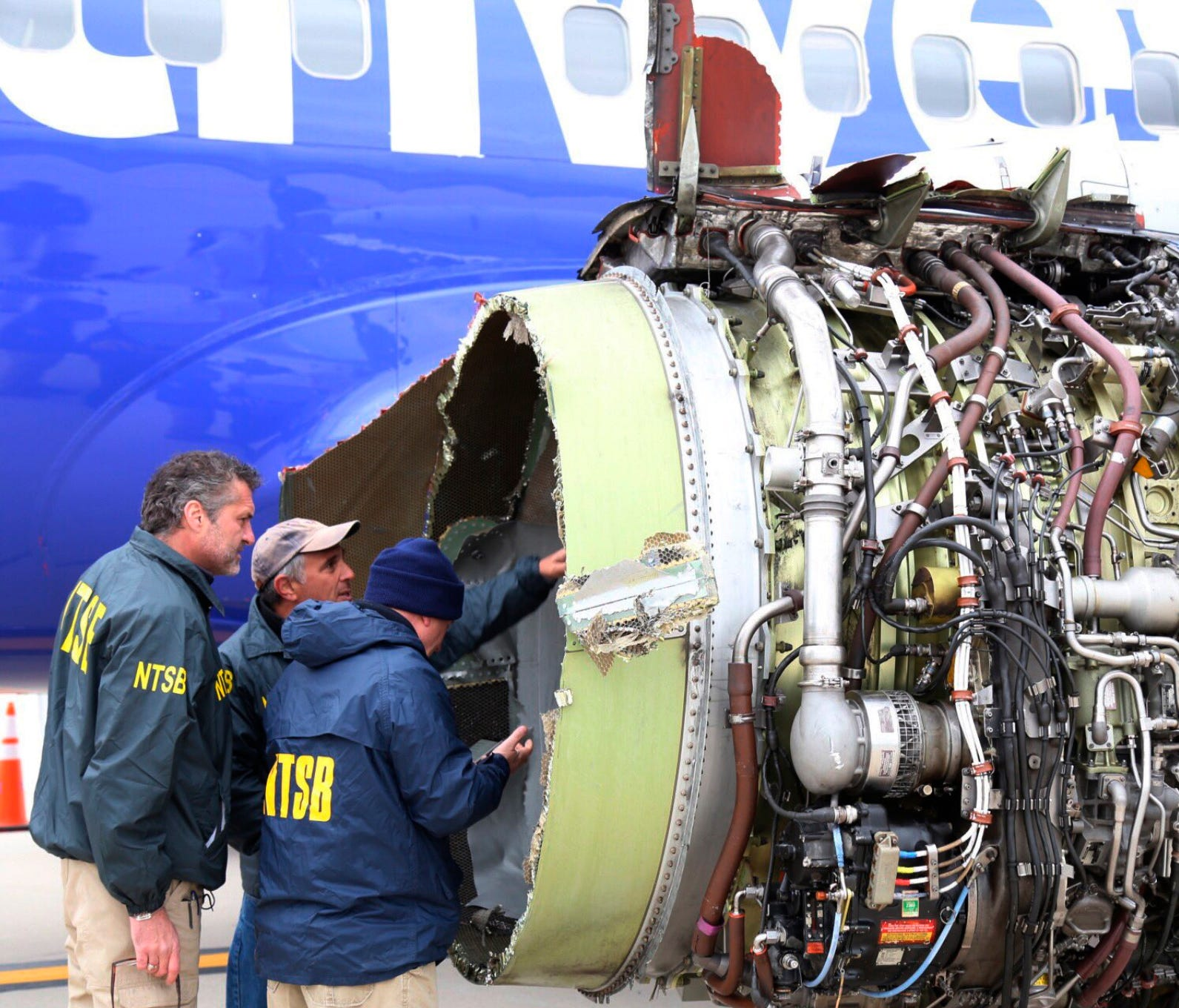 A National Transportation Safety Board investigator examines damage to the engine of Southwest Airlines Flight 1380 that made an emergency landing at Philadelphia International Airport in Philadelphia. A preliminary examination of the blown jet engin