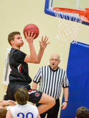 ADM's Tajen Ross (5) drives in for a layup on Friday,