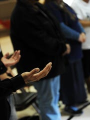 Hands raise in prayer during a healing circle led by Jerry Tello two years ago in response to a number of shootings in Salinas. Local faith leaders gathered in Salinas Thursday to collaborate on what they can do to reduce violent crime in an area known for its high murder rate.