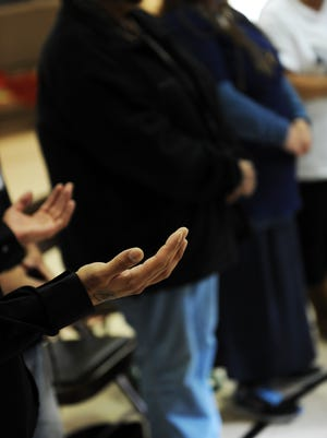 Hands raised in prayer late Monday afternoon at Jesse Sanchez Elementary School. More than thirty community leaders met for a healing circle led by Jerry Tello in response to a number of shootings in Salinas.