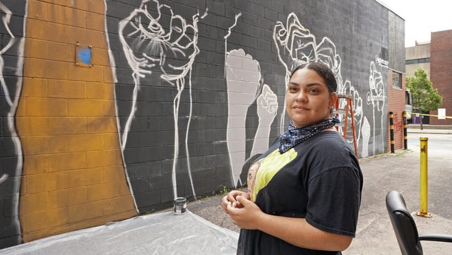 """Artist Angela Gonzalez works on a mural on the side of the Providence Student Union building, across the street from Classical High School, in July. """"These kids are the change,"""" she said, of the students who will see her work when they return to school. """"If we can't teach them to be role models now, they won't be."""""""