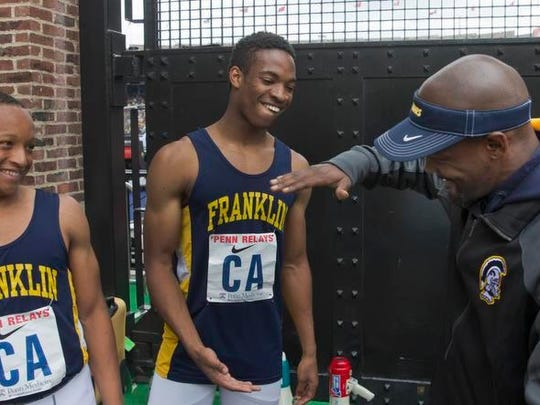 Franklin track coach Dashaun Gourdine congratulates NIle Uzzell after Franklin won the 4x100 large schools final at the Penn Relays.