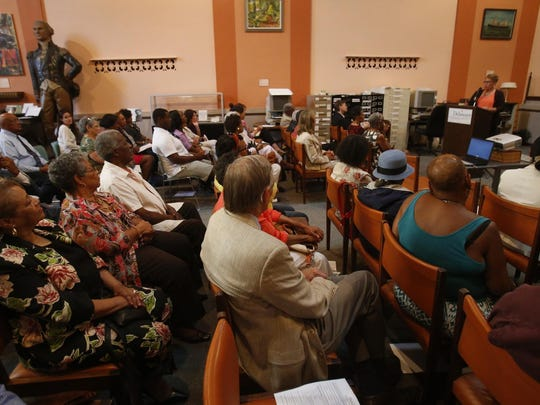 """Attendees listen as Dr. Patrice Gilliam-Johnson speaks about her father, James H. Gilliam Sr., during a showing of the latest """"Voices of the Elders"""" documentary about him at the Delaware Historical Society research library in Wilmington."""