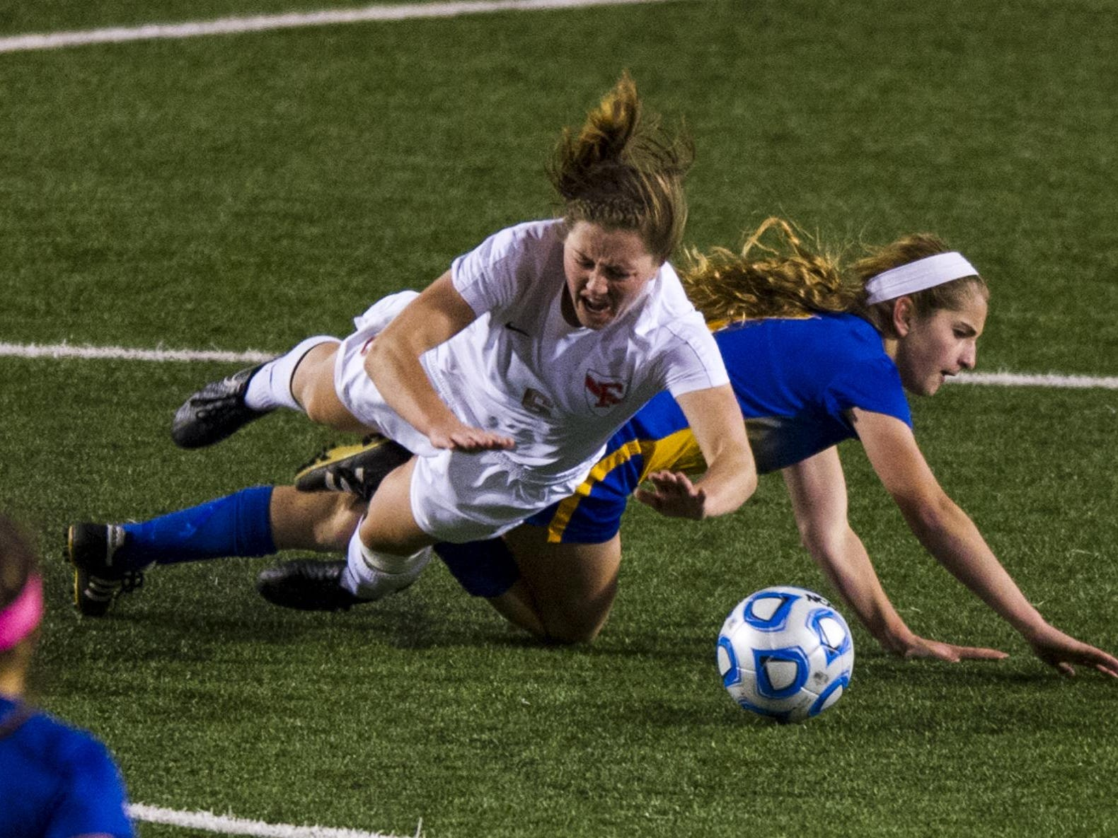 Fishers High School junior Brady Riley (6) crashes to the turf after colliding with Carmel High School sophomore Emily Roberts (7) during the second half of action. Carmel High School competed against Fishers High School in the 2014 IHSAA Class 2A Girls' Soccer State Championship game at Michael A. Carroll Track and Soccer Stadium in Indianapolis. Fishers defeated Carmel 1-0.