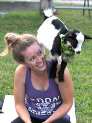 A goat stands on back of Leslie Murray during a goat
