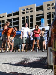Festival-goers create a giant beer bottle out of used bottles during the 2014 Sun City Craft Beer Festival. The fest will not only feature music and entertainment, but games and food.