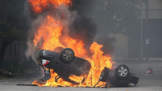 Protesters overturned and set fire to several cars in the parking lot across from the City Public Safety Building. JAMIE GERMANO/ROCHESTER DEMOCRAT AND CHRONICLE