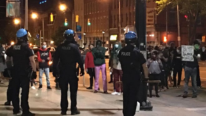 Erie police confront demonstrators at North Park Row and State Street in downtown Erie on Saturday. The demonstrators vandalized Erie City Hall and hurled bottles and fireworks at police. The late-night demonstration was very different from a peaceful protest that took place at 6 p.m. that evening nearby at Perry Square, also in downtown Erie.