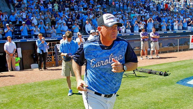 FILE - In this May 26, 2013, file photo, North Carolina head coach Mike Fox takes the field to accept the championship trophy following UNC's 4-1 win over Virginia Tech in an Atlantic Coast Conference NCAA college baseball game in Durham, N.C. UNC announced Friday, Aug. 7 2020, that Fox would retire after 22 seasons at his alma mater that included seven trips to the College World Series. Longtime assistant Scott Forbes is taking over the program.