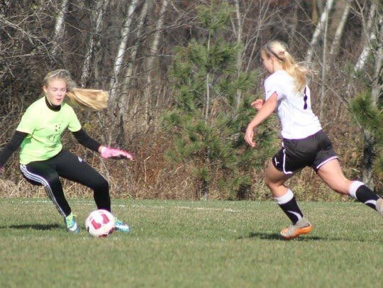 Abby Gemza chases down the ball as the oposing goalie