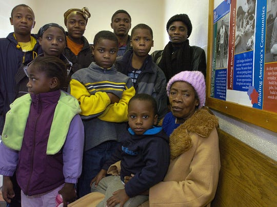 The large, extended Blamo family from war-torn Liberia poses after church at Christ Lutheran Church in Lansing in 2005. Top row, from left, are Kanrwea Blamo, 11, March Blamo, 14, Weah Blamo, 19, and Orena Blamo. Middle Row, Agnes Blamo, 9, Ba Blamo, 7, and Bob Blamo, 12. Bottom row are Edith Blamo, 5, Try Blamo, 2, and Nancy Blamo. Ba has grown up to be a star running back on the Grand Ledge football team.