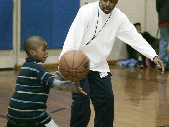 Raymire Briscoe, 7, reaches for a pass as Rodney Burruss Sr. keeps an eye on him during a coed basketball clinic for Kuumba Academy students at the Salvation Army gym in Wilmington in 2006. Briscoe, now 15, was charged with committing first-degree murder at the age of 14.