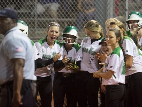 The Fort Myers softball cheers for Josey Mayer after she hit a homerun in the sixth inning against North Fort Myers on Tuesday, March 24, 2015, at Fort Myers High School.