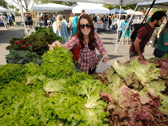 BreeAnn Souza of Visalia shops for lettuce at the K.M.K. Farms booth during the Visalia Farmers Market on Saturday.