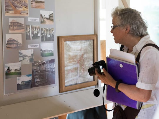 Elisabeth Furter Sermersheim, a Swiss resident and the niece of Viktor Riether, looks at old barracks photos from previous generations of Fort Custer.