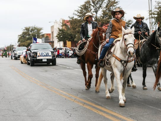 Paraders make their way down Concho Avenue during the