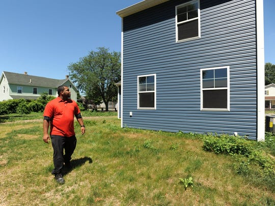 Stephen Walker looks at his home, built by Habitat for Humanity, in downtown Dover on Thursday. Five dwellings are being built on the block.