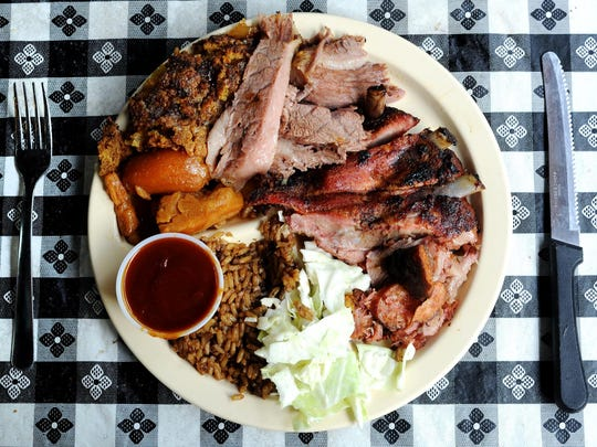 A plate full of brisket, pork ribs and pork loin stuffed with sausage fresh from the pit along with side dishes of rice dressing, coleslaw, yams and peach cobbler is ready to be enjoyed in the dining room at A & B Henderson's BBQ in Lafayette.