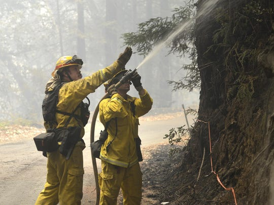 Cal Fire firefighters extinguish hotspots while fighting the Soberanes Fire in Palo Colorado Canyon on the northern Big Sur Coast on Tuesday July 26, 2016 in Big Sur. California's signature parks along the Big Sur coastline that draw thousands of daily visitors were closed Tuesday as one of the state's two major wildfires threatened the scenic region at the height of the summer tourism season.