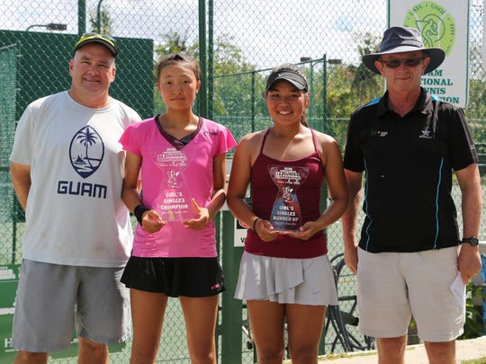 Japan's Shiho Tsukuda and No. 1 Sara Tsukamoto of the United States, finalists of the Girls Singles event of the 2016 Chuck E. Cheese's Junior Championships, pose for a photo after a short awards ceremony following the event's final match at the Rick Ninete Tennis Center in Hagåtña. Tsukuda won 6-1, 6-1. In the photo are, from left to right, Tournament Director Torgun Smith, Tsukuda, Tsukamoto, and Patrick O'Rourke, Tournament Referee.