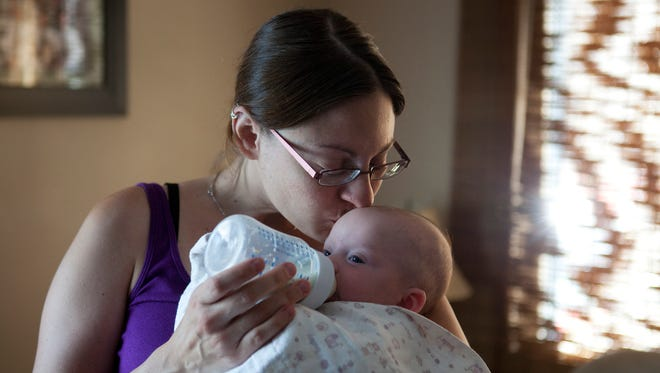 "Amy Pierson kisses her 3-month-old daughter, Charity, as she feeds her at her home in East Rochester on Thursday. Amy is the wife of Daryl Pierson, the Rochester police officer who was shot and killed on Wednesday night. ""He lived a hero, he didn't have to die to be a hero,"" said Amy's mother, Joan Evans. ""He was a solid, strong guy ... the best, best dad, a hero daddy."""