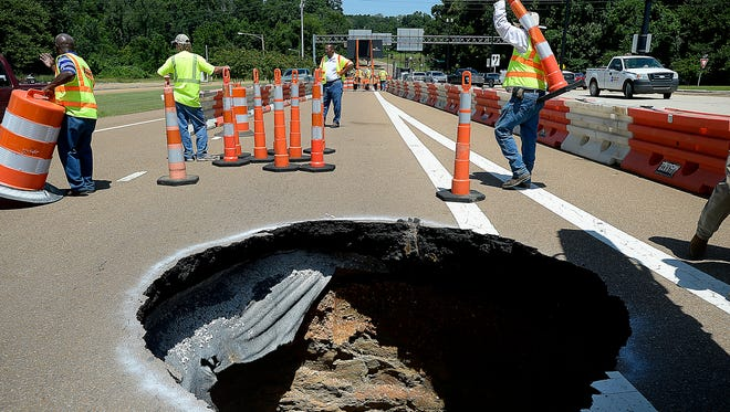 In this photo taken on Wednesday, Aug. 13, 2014, Mississippi Department of Transportation employees move safety barriers around a sinkhole that developed in the turning lane of John R. Junkin Drive to Route 61 South in Natchez, Miss. (AP Photo/The Natchez Democrat, Sam Gause)