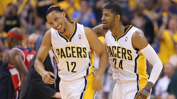Pacers Evan Turner and teammate Paul George head toward the bench during a break in the first half of action. Indiana Pacers play the Washington Wizards in the Eastern Conference semi-final game Tuesday, May 13, 2014, evening at Bankers Life Fieldhouse.