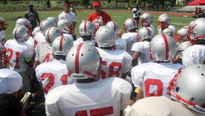 Perth Amboy first year football coach Brad Bishop speaks with his players during preseason practice, Wednesday, August 20, 2014, in Perth Amboy, NJ. Photo by Jason Towlen