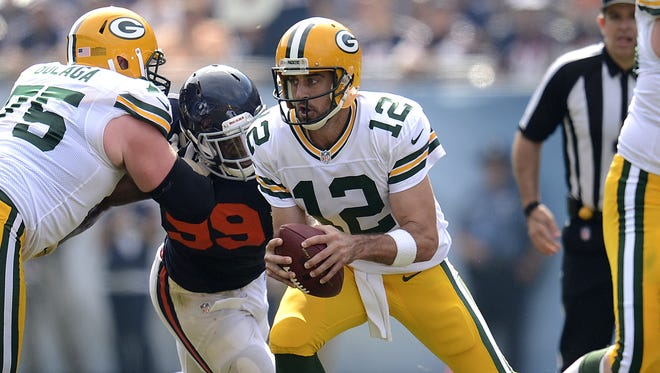 Green Bay Packers quarterback Aaron Rodgers (12) takes off while being pressured by Chicago Bears defensive end Lamarr Houston (99) in the third quarter during Sunday's game at Soldier Field in Chicago. Evan Siegle/Press-Gazette Media/@PGevansiegle
