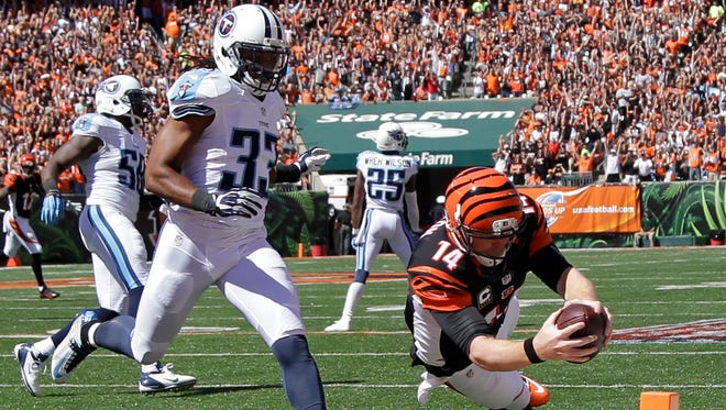 Cincinnati Bengals quarterback Andy Dalton, right,  dives into the end zone for a touchdown past Tennessee Titans free safety Michael Griffin in the first half on Sunday.