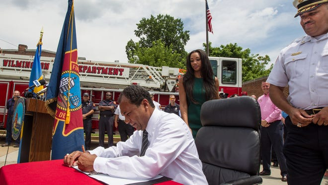 Mayor Dennis P. Williams signs a veto Friday overriding a Wilmington City Council bill cutting vacant firefighter positions.
