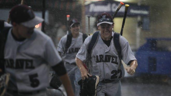 Caravel baseball players run through the rain following the end of the rain shortened A.I. du Pont - Hodgson quarterfinal game at Frawley Stadium on Tuesday