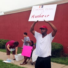 "Lamont Jones holds up a sign reading ""Darren Wilson is a Murderer,"" on Aug. 23 in St. Louis. Jones was reacting to a rally supporting Wilson, the white officer who shot unarmed, black 18-year-old Michael Brown in Ferguson, Mo. Like many Americans, Jones has formed concrete opinions about the case."