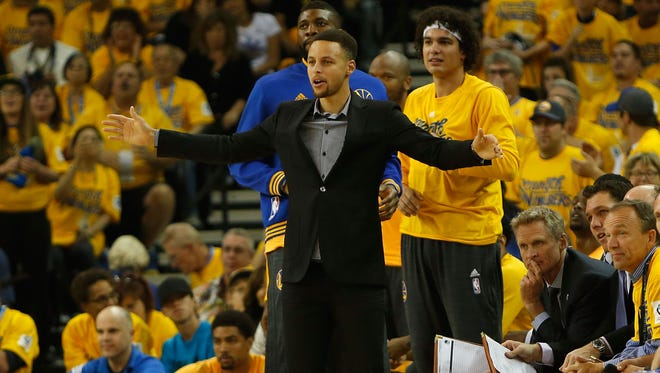 Injured point guard Stephen Curry #30 of the Golden State Warriors supports his team from the bench in Game Two.
