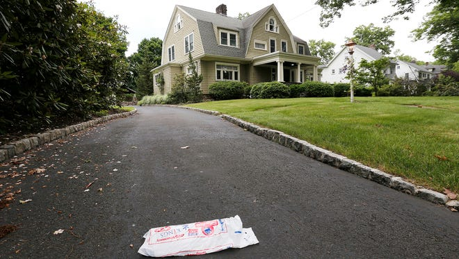 """In this June 25, 2015, file photo, a newspaper rests on the driveway of the home of Derek and Maria Broaddus in Westfield, N.J. The couple wants to demolish the house after they claim they were stalked by an anonymous creepy-letter writer known as """"The Watcher"""" has filed a lawsuit against their town. (AP Photo/Julio Cortez, File)"""