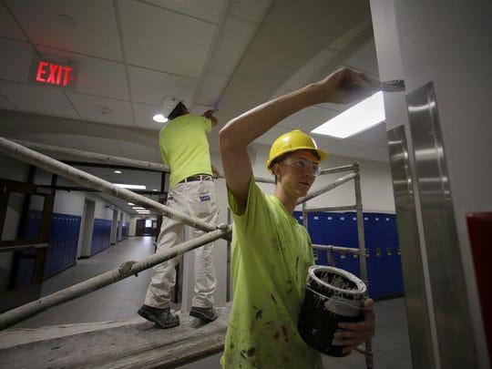 Craig Raatz and Tim Filtz paint one of the hallways