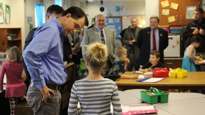 Gov. Scott Walker talks with a student April 11 during a tour of Mountain Bay Elementary School in Weston.