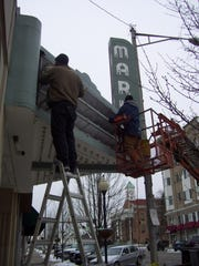 Workers installing a new electronic sign during the renovation of the Markay from a movie theater to the new Cultural Arts Center.