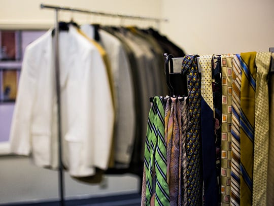 Coats and ties are neatly arranged on racks during