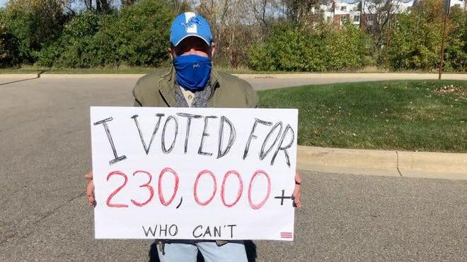 """Troy resident Lloyd Austin, 61, walked for hours back and forth outside the center holding a sign that said, """"I voted for 230,000+ who can't,"""" referring to the COVID-19 death toll."""